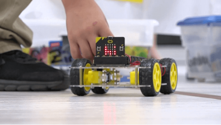 middle school students show off coding skills in robotic vehicle obstacle course.